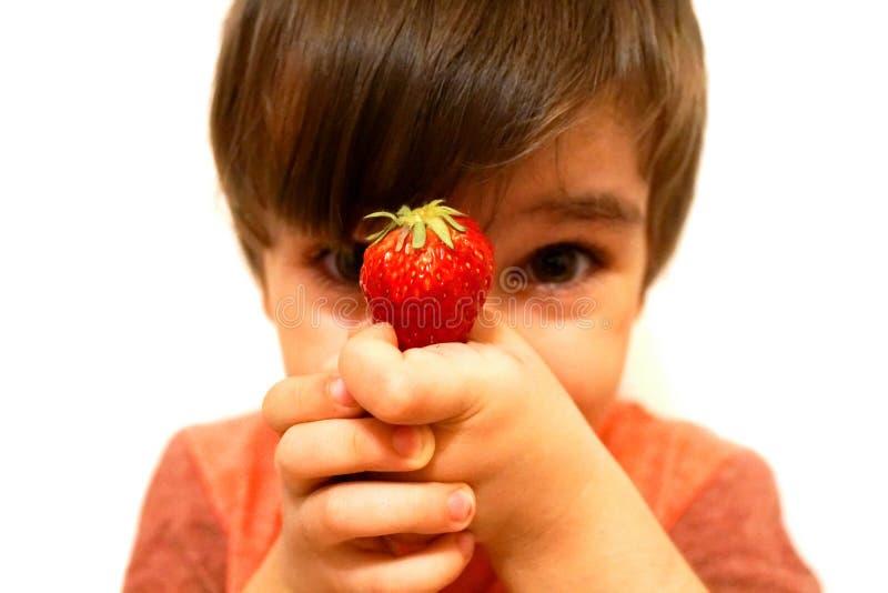 Pojken rymmer i hans hand en röd jordgubbe fotografering för bildbyråer
