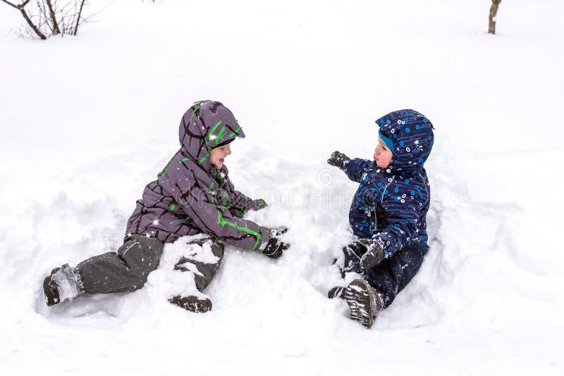 Pojken rymmer insnöade händer aktiv vintertid utomhus royaltyfri foto