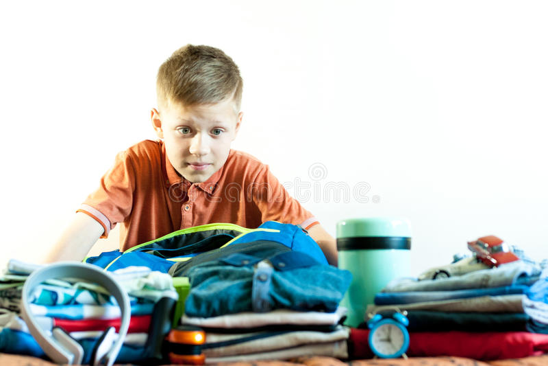 Pojken samlar hans saker på turen royaltyfri fotografi