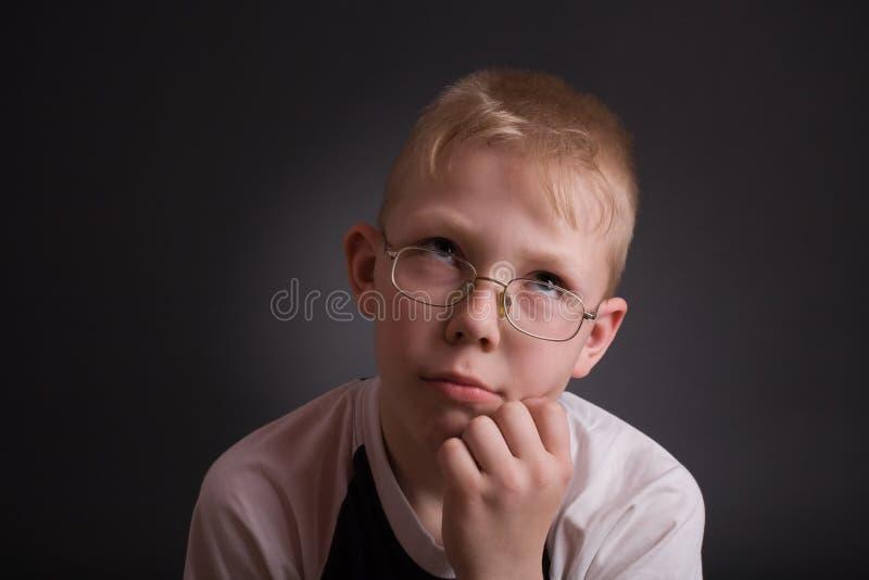 Pojken ser upp, och stöttan som hans huvud räcker by arkivfoton