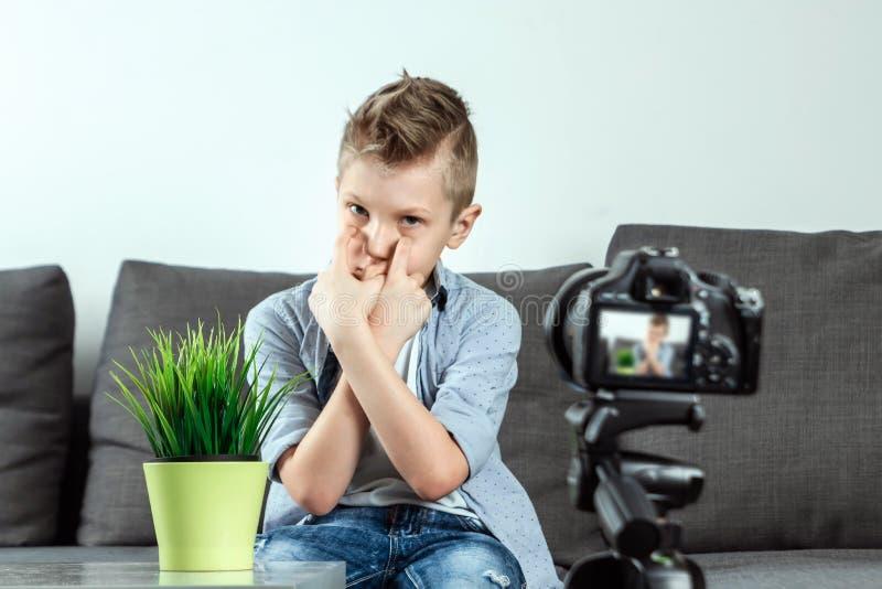 Pojken sitter framme av en SLR kamera, n?rbild Blogger som blogging, teknologi, f?rtj?nster p? internet kopiera avst?nd royaltyfri foto