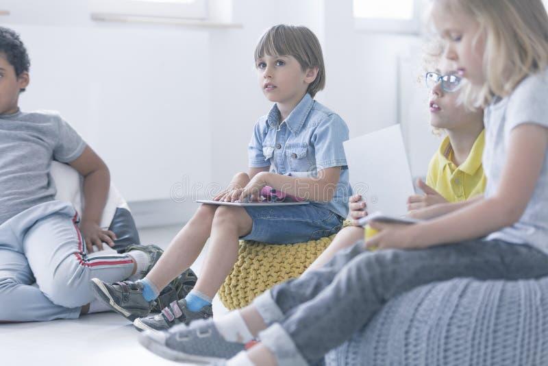 Pojken sitter i en grupp av barn arkivfoton