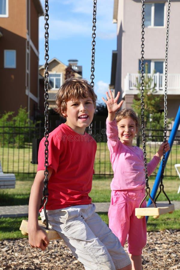Pojken sitter på swing, och flickan vågr henne handen royaltyfria foton