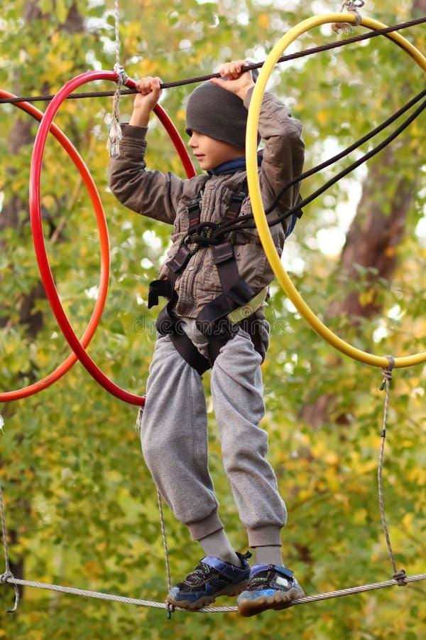 Pojken som övervinner hinderkurs i det utomhus- repet, parkerar bland höstlövverk arkivbilder