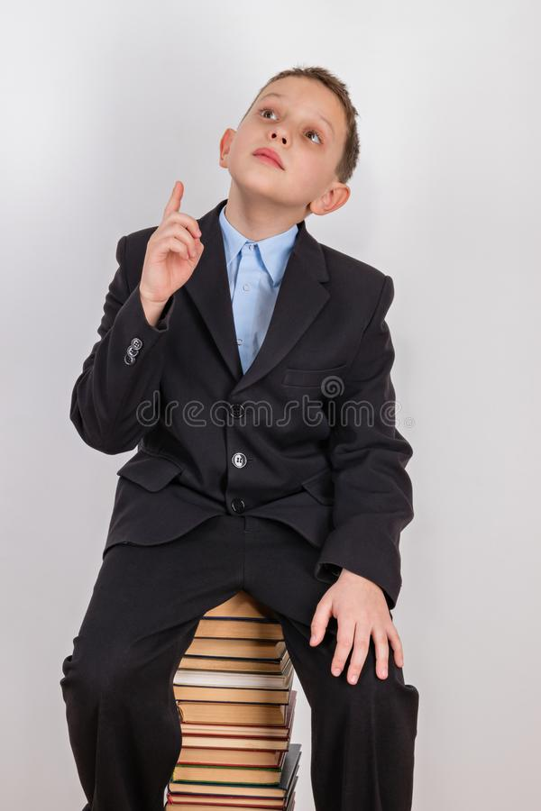 Pojken, som besöktes av idén, sitter på en bunt av böcker med ett lyftt pekfinger fotografering för bildbyråer