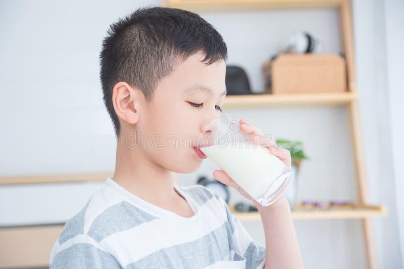 Pojken som dricker ett exponeringsglas av, mjölkar för frukost royaltyfri fotografi