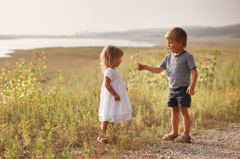 Pojken som ger buketten av våren, blommar till den lyckliga flickan royaltyfria bilder