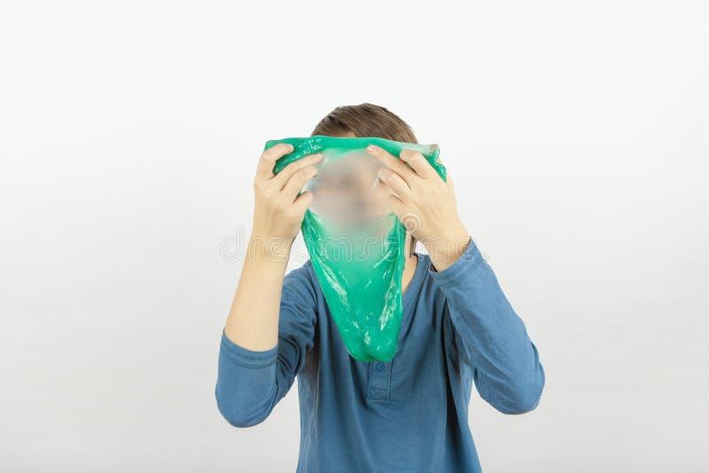Pojken som håller en grön glimt framför sitt ansikte royaltyfria bilder