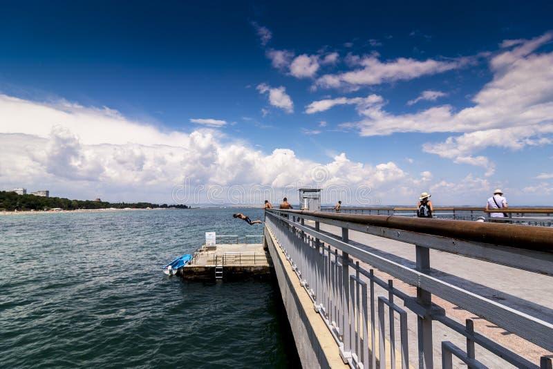 Pojken som hoppas från bron till vatten sommargyckel i varmt väder Hoppet bevattnar in arkivfoto