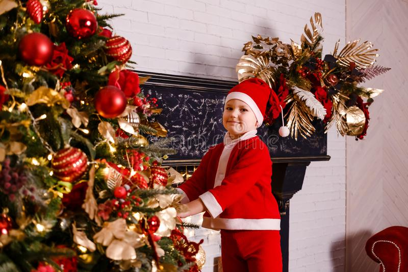 Pojken som kläs som Santa Claus, dekorerar en julgran royaltyfri foto