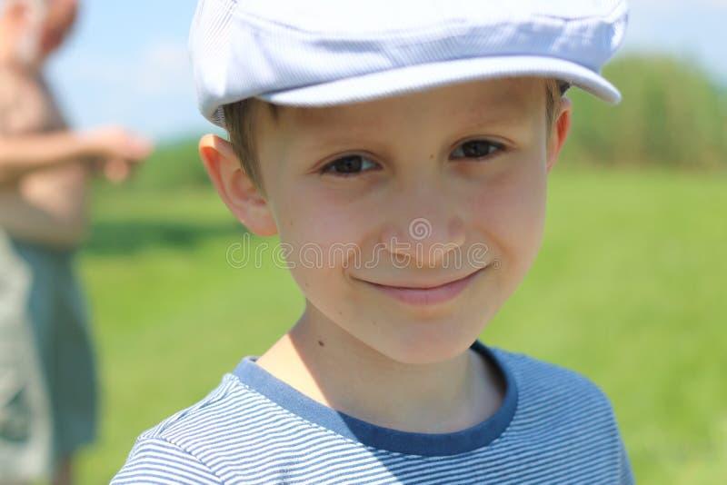 Pojken som ler med hatten fotografering för bildbyråer