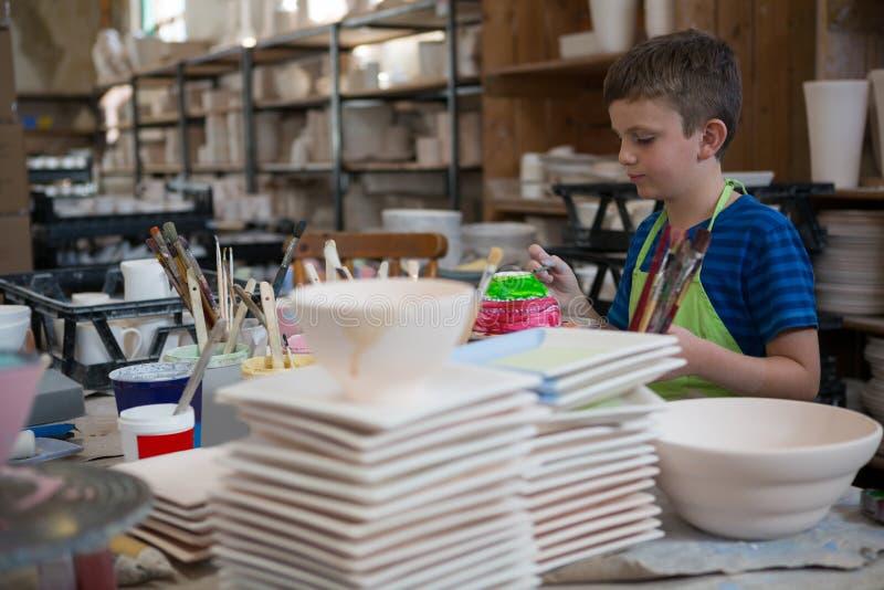 Pojken som målar en bunke i krukmakeri, shoppar royaltyfri foto