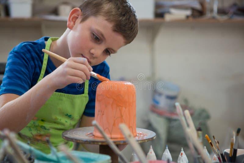 Pojken som målar en bunke i krukmakeri, shoppar arkivbild