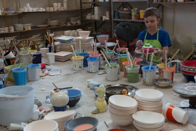Pojken som målar en bunke i krukmakeri, shoppar royaltyfri bild