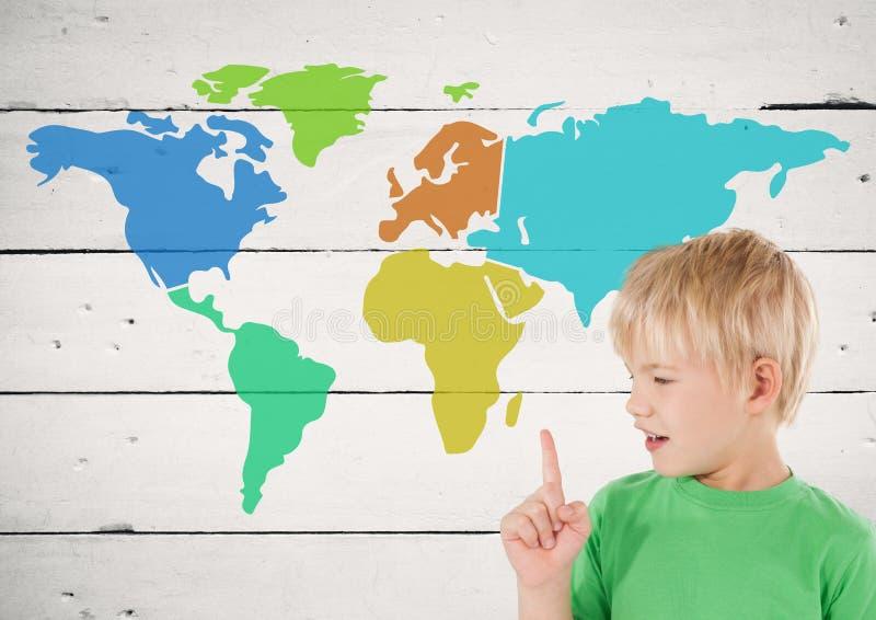 Pojken som pekar på den färgrika översikten med målarfärg, stänker på wood bakgrund royaltyfri bild