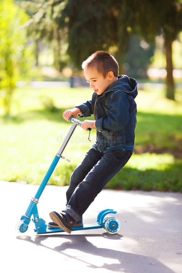 Pojken som rider en sparkcykel parkerar in royaltyfria foton