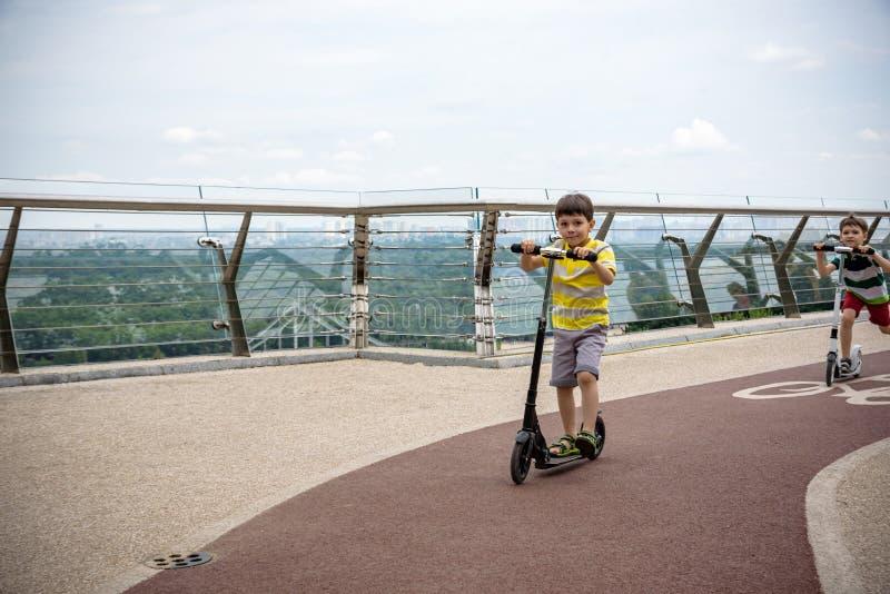 Pojken som rider hans sparkcykel i lokalen, parkerar solig sommar arkivbilder