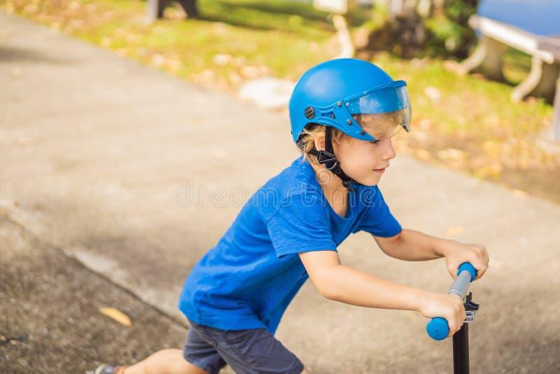 Pojken som rider sparkcyklar som är utomhus- i, parkerar, sommartid Ungar är lyckligt spela utomhus royaltyfria foton