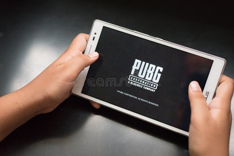 Pojken som rymmer en digital minnestavla som spelar online-mobilleken, kallade PUBG arkivfoton