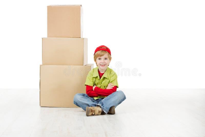 Pojken som sammanträde av paketerar framme, boxas royaltyfri foto