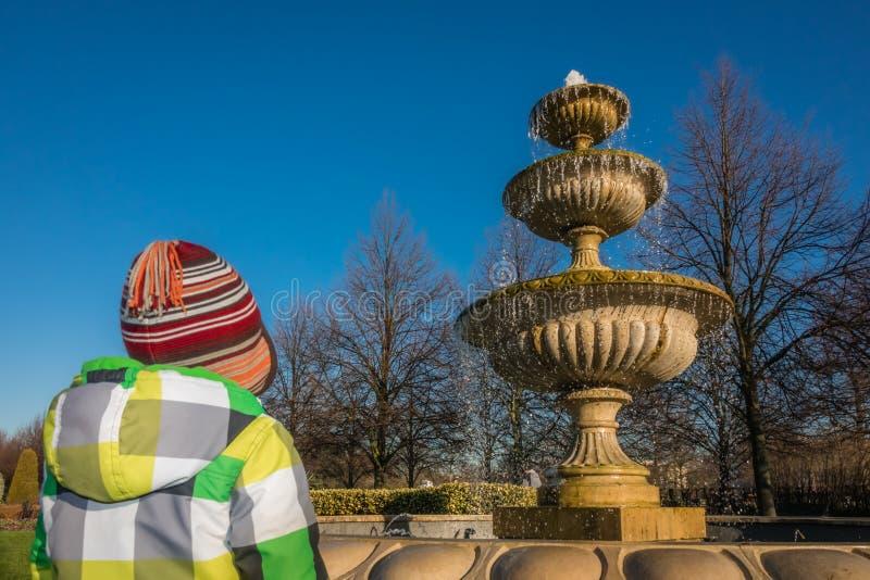 Pojken som ser springbrunnen i regenter, parkerar royaltyfri bild
