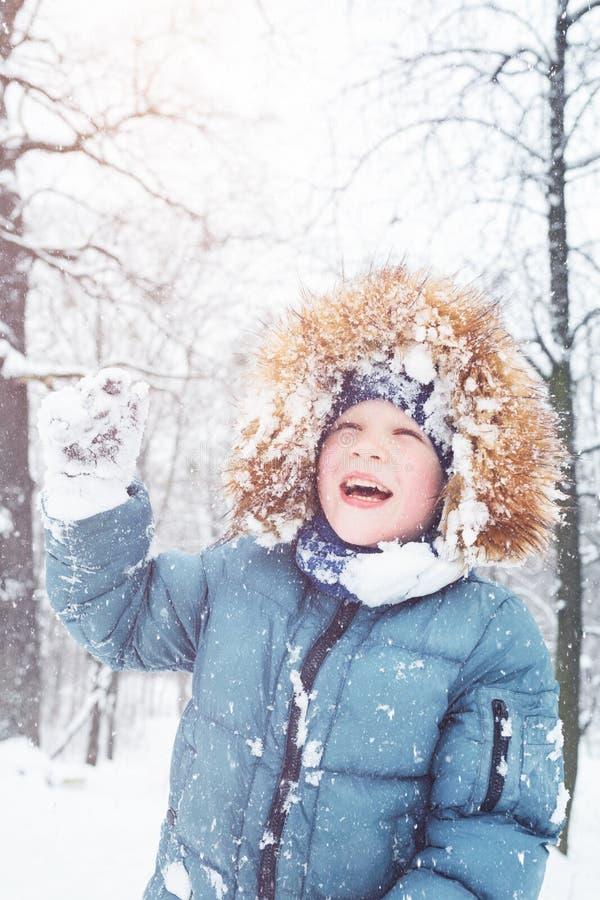 Pojken som spelar med insnöad vinter, parkerar royaltyfria foton