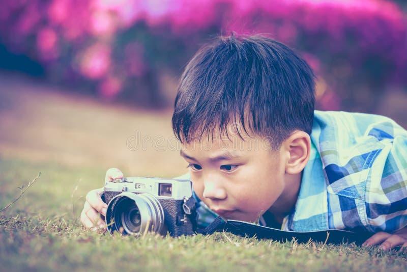 Pojken som tar fotoet vid kameran, den undersökande naturen på, parkerar Förtjusande c royaltyfri bild
