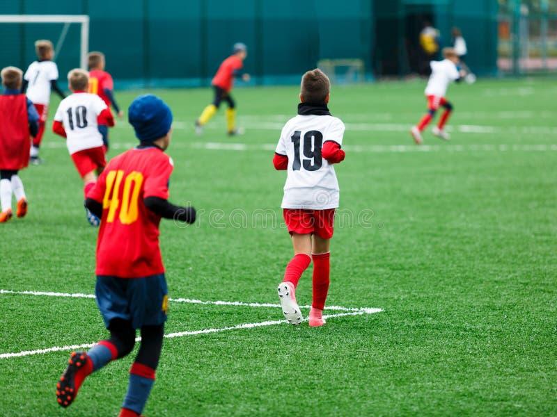 Pojken sparkar fotbollbollen Pojken jagar bollen på grönt gräs fotbollsspelare i den vita och röda skjortan dregla för pojkar arkivfoton