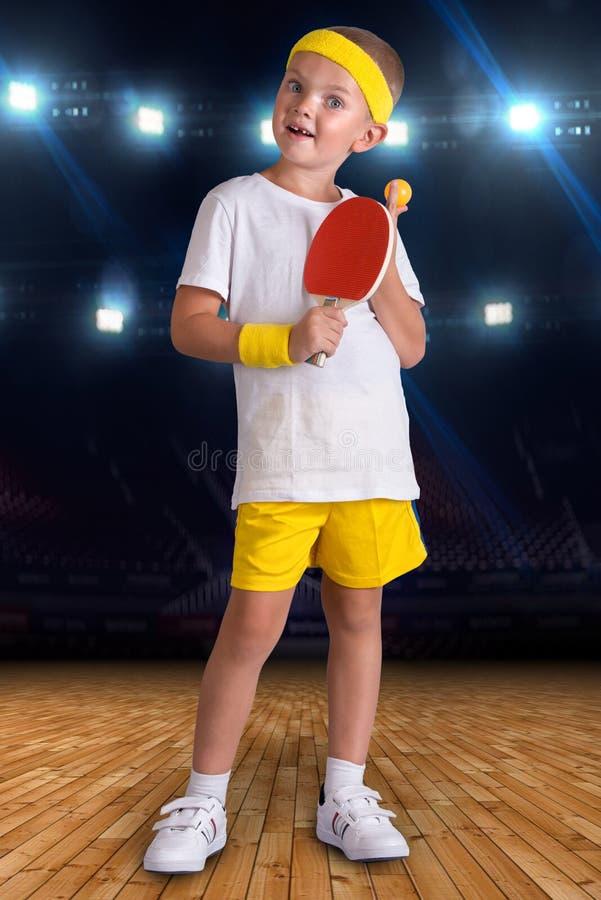 Pojken spelar bordtennis i sportkorridoren arkivbild