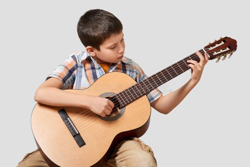 Pojken spelar den akustiska gitarren fotografering för bildbyråer