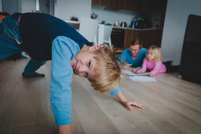 Pojken spelar hemmastatt, medan fadern gör läxa med dottern arkivbilder