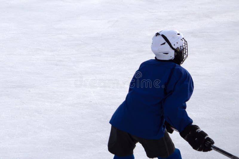 Pojken spelar hockey på en gata som åker skridskor isbanan En pojke på gatan som spelar hockey royaltyfri bild