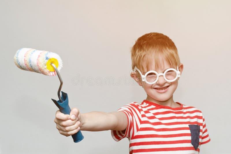 Pojken spelar i husmålaren Stående Rulle för att måla fotografering för bildbyråer