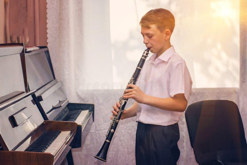 Pojken spelar klarinetten nära det svarta pianot vid fönstret Musicology, musikutbildning och utbildning royaltyfri fotografi
