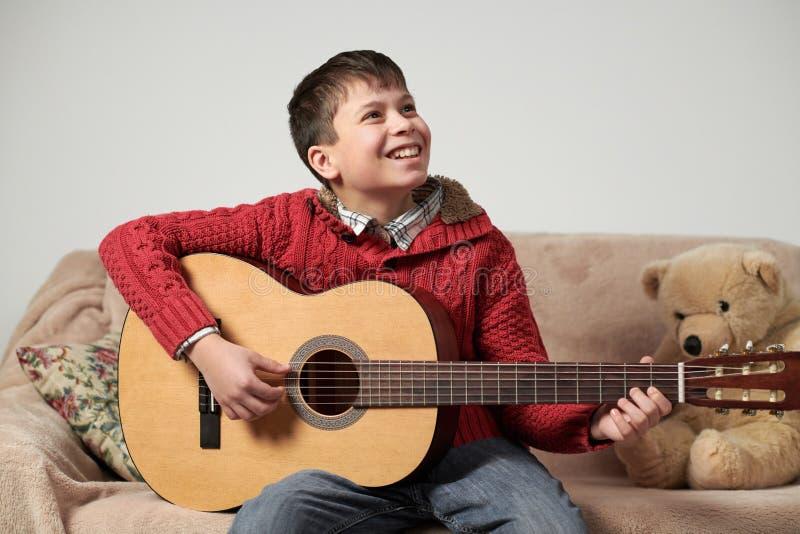 Pojken spelar med en akustisk gitarr, sitter på soffan med en björnleksak arkivbilder