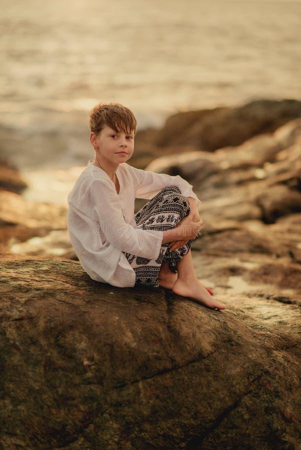 Pojken spelar på vaggar arkivbild