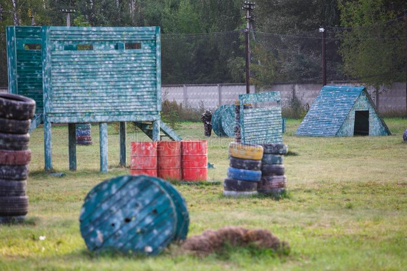 pojken spelar paintball på fältet två lag av paintballspelare i kamouflageform med maskeringar, hjälmar, vapen på fältet royaltyfria foton
