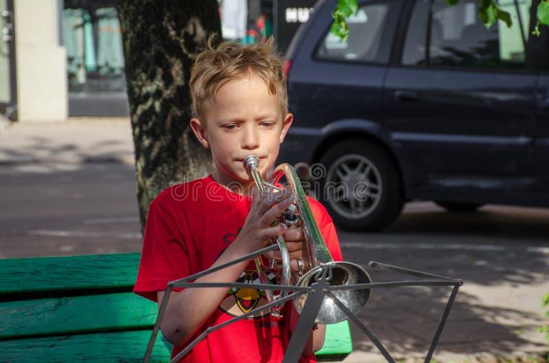 Pojken spelar trumpeten i gata arkivbild