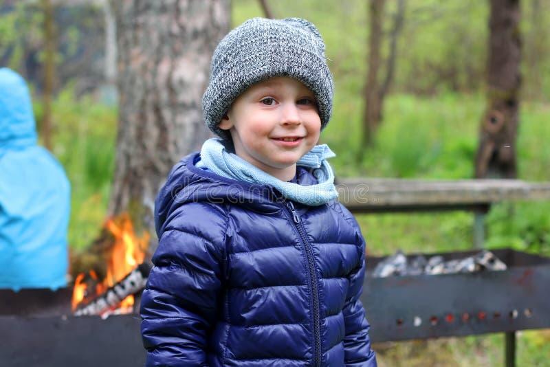 Pojken står i varm kläder och leenden Barn i landet i den kalla säsongen I bakgrunden ett galler eller en brasa royaltyfri bild