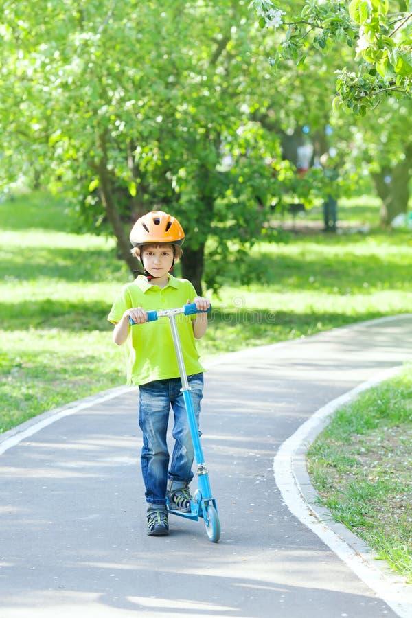 Pojken står med sparksparkcykeln på banan parkerar in arkivbilder
