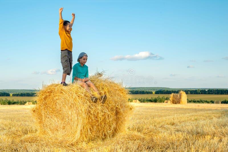 Pojken står på en höstack och lyfter joyfully hans händer upp till solen arkivfoto