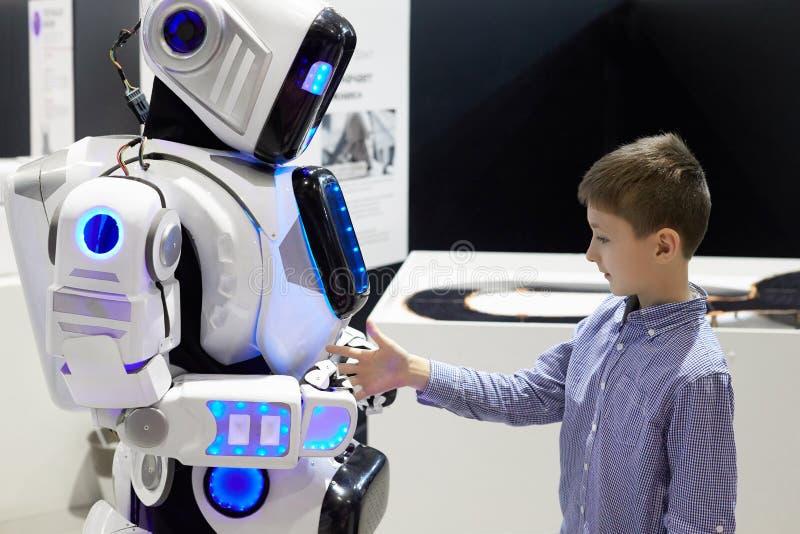 Pojken sträcker ut hans hand till roboten som ett tecken av vänner royaltyfri bild