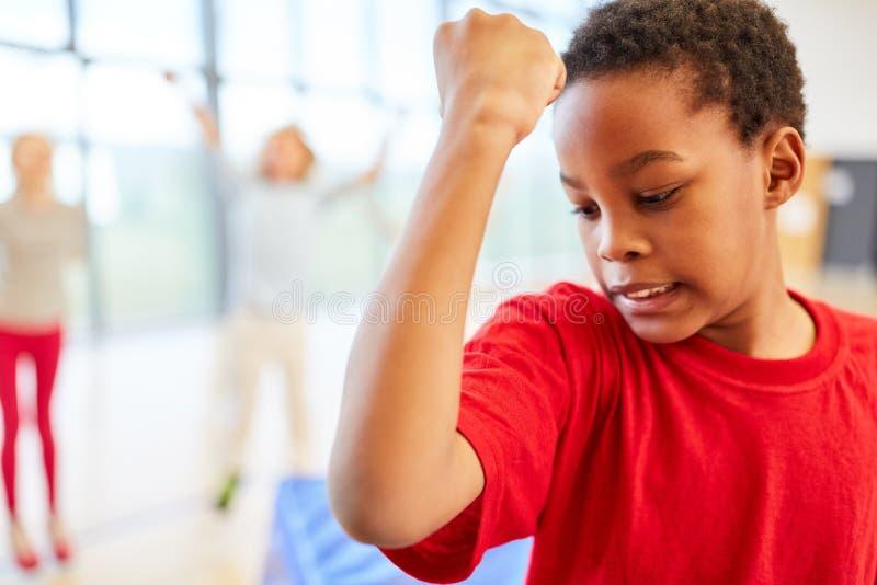Pojken stramar åt hans biceps arkivfoton