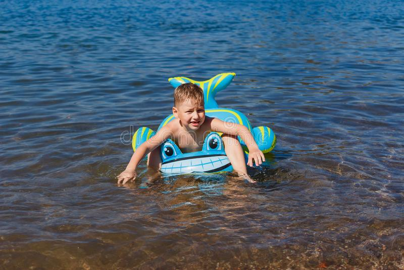 Pojken svävar på en rubber delfin i havet royaltyfria bilder