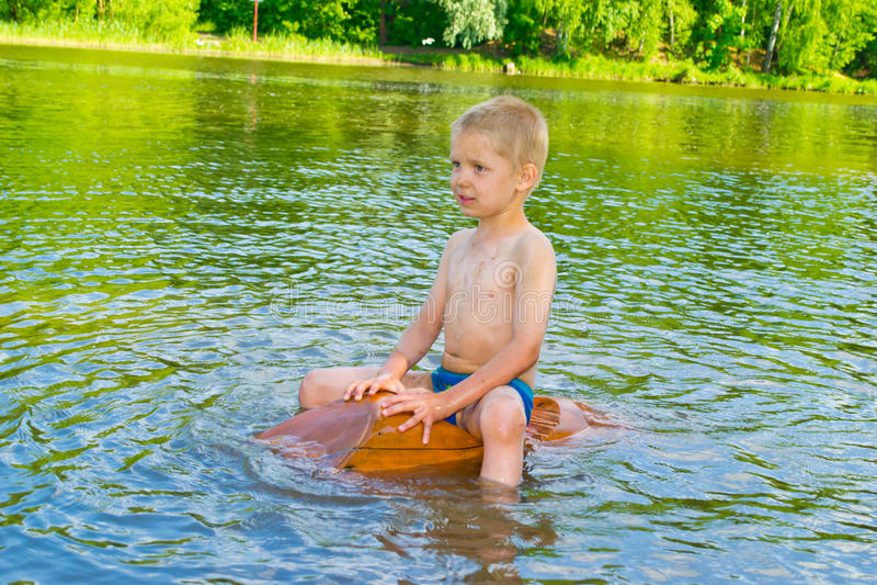 Pojken svävar på floden arkivbilder