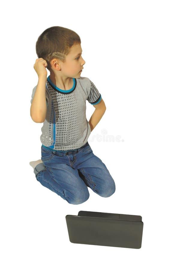 Pojken tänker med en bärbar dator fotografering för bildbyråer