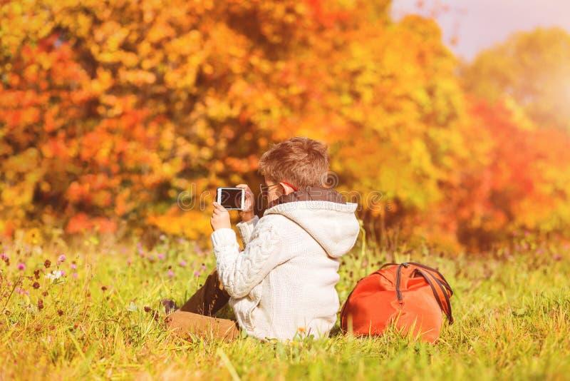 Pojken tar foto med mobiltelefonen av höstträd royaltyfri bild