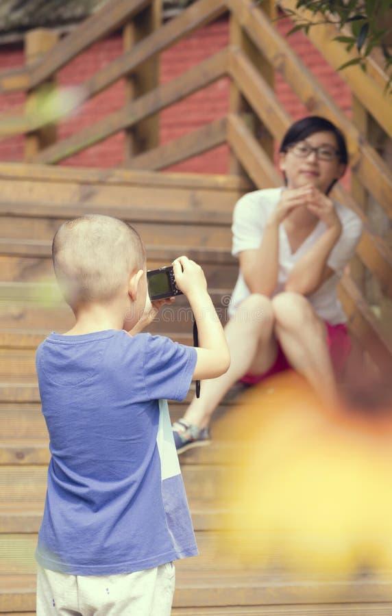 Pojken tar fotoet för moder royaltyfria bilder