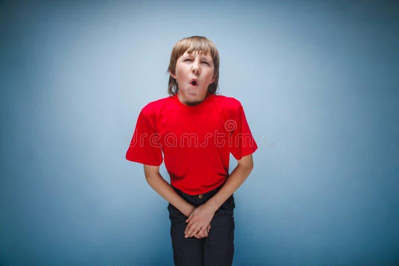 Pojken tonåring, tolv år i den röda skjortan önskar arkivbilder