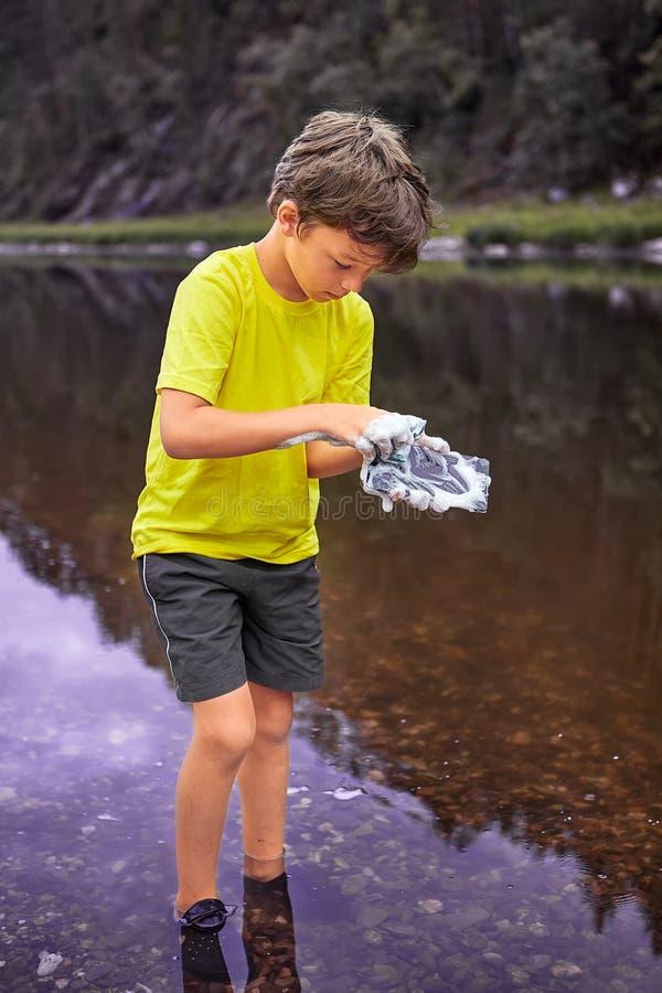 Pojken tvättar mobiltelefonen med skum royaltyfria bilder